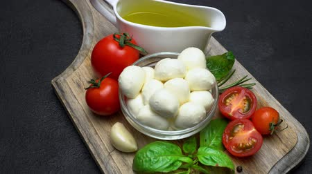 olivový olej : Ingredients for caprese salad - Mozzarella, tomatoes, basil leaves, olive oil