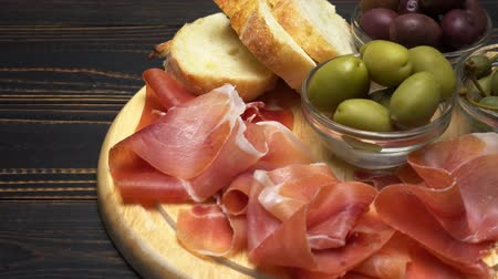 capers : sliced prosciutto on a wooden board and bread