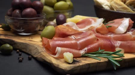 устроенный : sliced prosciutto on a wooden board and bread