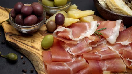 kapary : sliced prosciutto on a wooden board and bread