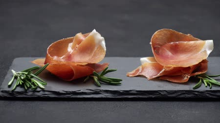 jamon : sliced prosciutto or jamon meat on dark concrete background