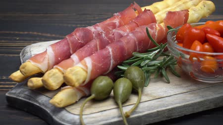 capers : italian grissini with prosciutto, capers and pepper on wooden cutting board