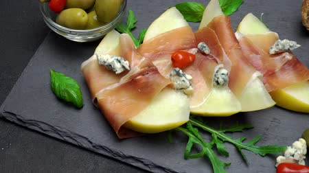 dorblu : sliced prosciutto and melon on a stone board Stock Footage