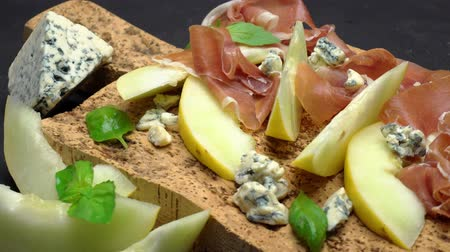 dorblu : sliced prosciutto and melon on a cork wooden board