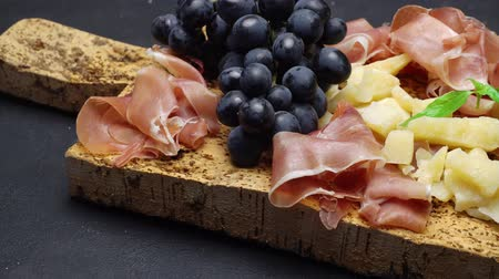 jamon : sliced prosciutto or jamon meat and cheese on cork wooden board Stock Footage