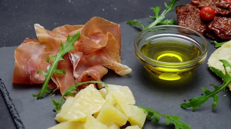 dried tomatoes : sliced prosciutto or jamon meat and cheese on concrete background Stock Footage