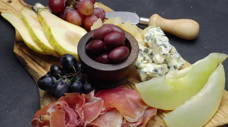dorblu : Meat and cheese plate antipasti snack with Prosciutto, melon, grapes and cheese