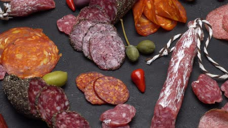 capers : salami and chorizo sausage close up on dark concrete background Stock Footage