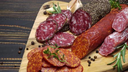 вылеченный : salami and chorizo sausage close up on wooden background Стоковые видеозаписи