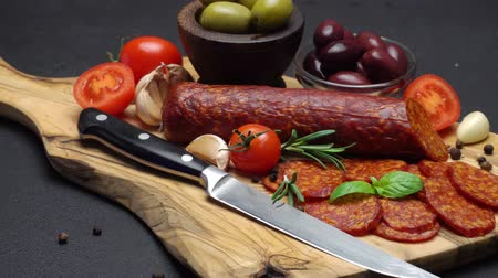 нож : salami and chorizo sausage close up on dark concrete background Стоковые видеозаписи