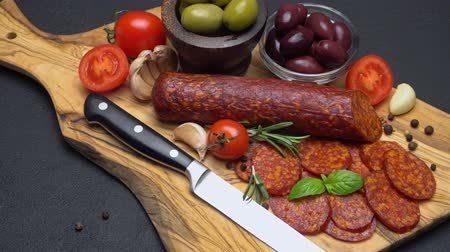 вылеченный : salami and chorizo sausage close up on dark concrete background Стоковые видеозаписи