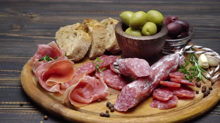 устроенный : sliced prosciutto and salami sausage on a wooden board