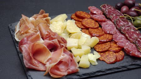 kapary : sliced prosciutto, cheese and salami sausage on stone serving board