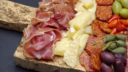 capers : sliced prosciutto, cheese and salami sausage on cork wooden cutting board