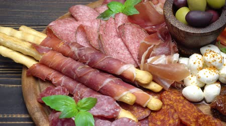 bread stick : Video of italian meat plate - sliced prosciutto, sausage and grissini
