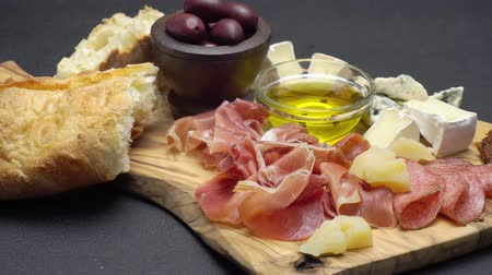 baharatlı alman sosisi : sliced prosciutto, cheese and salami sausage on a wooden board