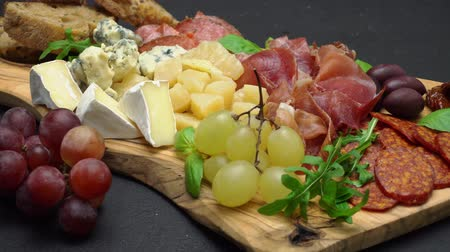устроенный : Meat and cheese plate antipasti snack with Prosciutto, melon, grapes and cheese