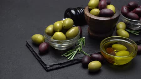 pickled : black and green olives and oil on stone serving board