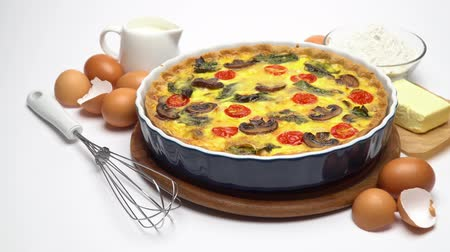 quiche : Baked homemade quiche pie in ceramic baking form, eggs and cream