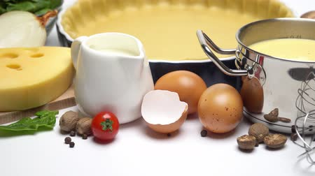 egg laying : shortbread dough for baking quiche tart in baking form and ingredients Stock Footage