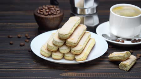 fasola : Italian Savoiardi ladyfingers Biscuits and cup of coffee on wooden background Wideo