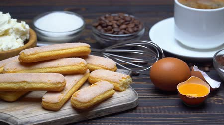 calorias : Ingredients for cooking tiramisu - Savoiardi biscuit cookies, mascarpone, cream, sugar, cocoa Stock Footage