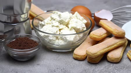 bolo de queijo : Ingredients for cooking tiramisu - Savoiardi biscuit cookies, mascarpone, cream, sugar, cocoa Stock Footage