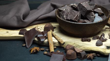bezuinigingen : Dark or milk organic chocolate pieces and truffle candies in wooden bowl on dark concrete background