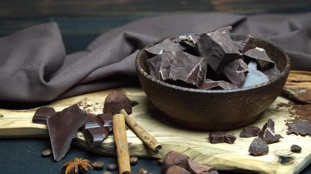 przyprawy : Dark or milk organic chocolate pieces and truffle candies in wooden bowl on dark concrete background