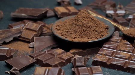 ложка : Dark or milk organic chocolate pieces and cocoa powder on dark concrete background