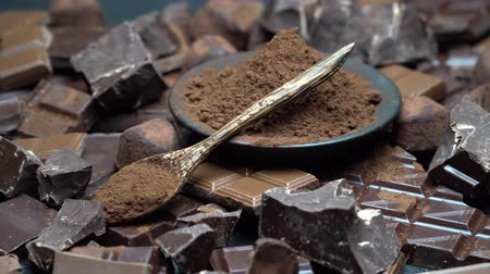 нарезанный : Dark or milk organic chocolate pieces, cocoa powder and truffle candies on dark concrete background
