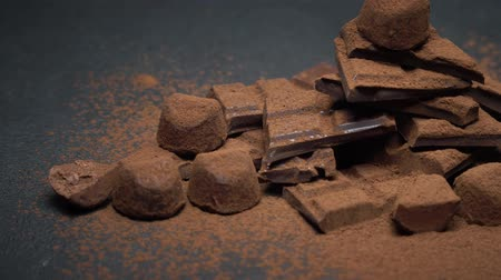amargo : Dark or milk organic chocolate pieces, cocoa powder and truffle candies on dark concrete background