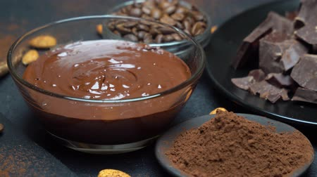 przyprawy : Melted chocolate or Hazelnut spread in glass bowl and chocolate pieces on dark concrete background