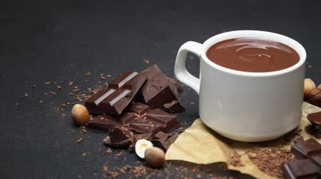grated : Cup of hot chocolate and pieces of chocolate on dark concrete background