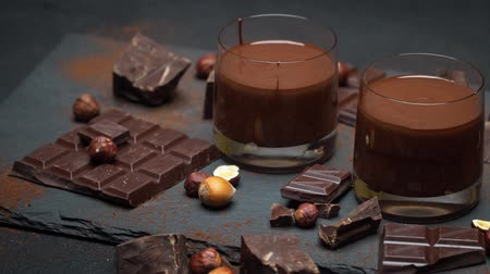 caloric : glass bowl of chocolate cream or melted chocolate, pieces of chocolate and hazelnuts