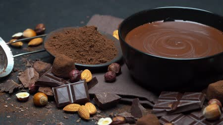 caloric : ceramic bowl of chocolate cream or melted chocolate, nuts and pieces of chocolate
