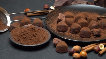 çatallar : Chocolate truffles candies, chocolate pieces and cocoa powder on dark concrete background