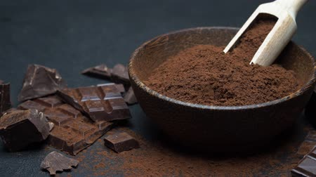 fasola : Dark Chocolate chunks and cocoa powder in wooden bowl on dark concrete background