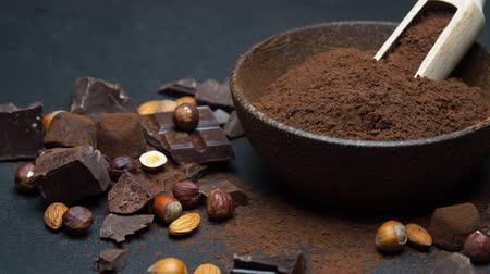 fasola : Dark Chocolate chunks, nuts and cocoa powder in wooden bowl on dark concrete background Wideo