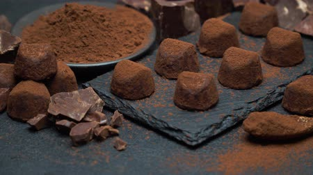 segurelha : classic chocolate truffles and pieces of chocolate on dark concrete background Stock Footage