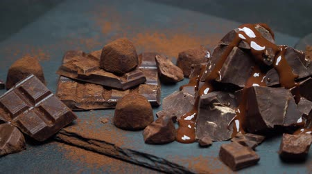 amargo : dark or milk chocolate pieces, chocolate syrup and truffle candies on dark concrete background