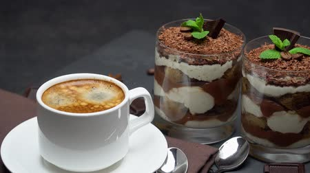 serving board : Classic tiramisu dessert in a glass and cup of coffee on dark concrete background
