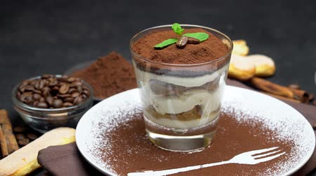 przyprawy : Classic tiramisu dessert in a glass and cup of coffee on dark concrete background