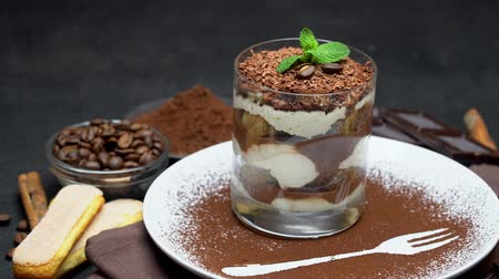 fasola : Classic tiramisu dessert in a glass and cup of coffee on dark concrete background