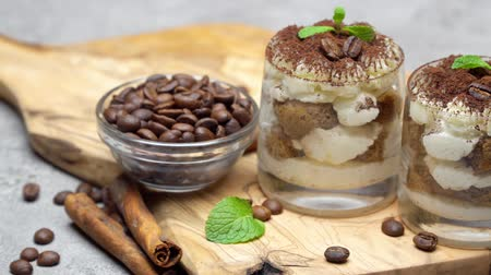 przyprawy : Classic tiramisu dessert in a glass on dark concrete background