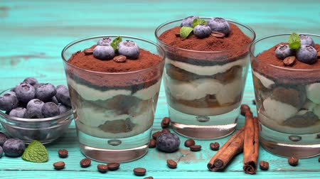 fasola : Classic tiramisu dessert in a glass with blueberries on blue wooden background