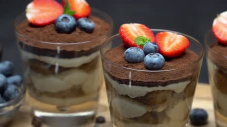 Classic tiramisu dessert with blueberries and strawberries in a glass on dark concrete background Stock Footage