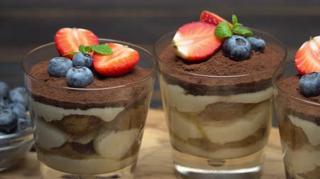 çatallar : Classic tiramisu dessert with blueberries and strawberries in a glass on wooden background
