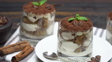 fincan tabağı : Classic tiramisu dessert in a glass on wooden background Stok Video