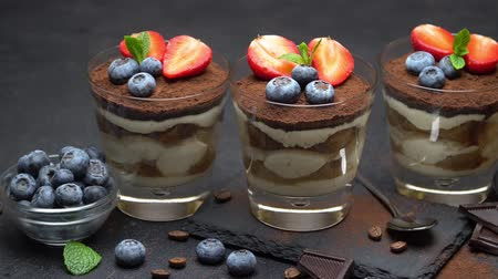 Classic tiramisu dessert with blueberries and strawberries on stone serving board on concrete Stock Footage